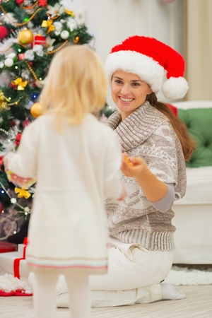 Baby helping mother decorate Christmas tree photo