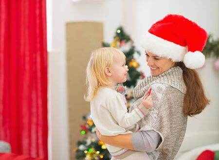 Happy young mother holding baby near Christmas tree Stock Photo - 16577947