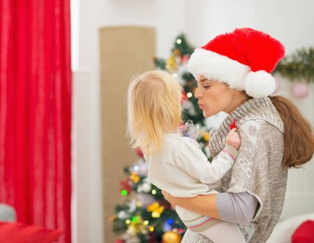 Mother kissing baby in front of Christmas tree Stock Photo - 16577959
