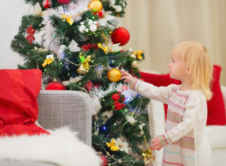 Baby touching Christmas ball on Christmas tree Stock Photo - 16577977