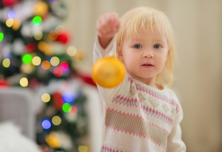Baby holding Christmas ball near Christmas tree Stock Photo - 16578000