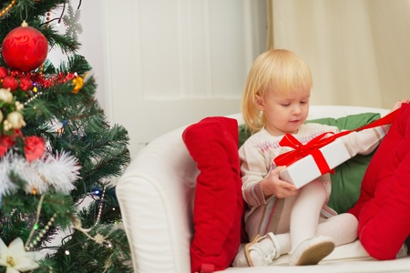 baby open present: Baby sitting on chair and open Christmas present box Stock Photo