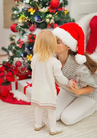 Mother kissing baby near Christmas tree photo