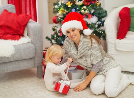 Baby sitting near mother and open Christmas present box Stock Photo - 16577978