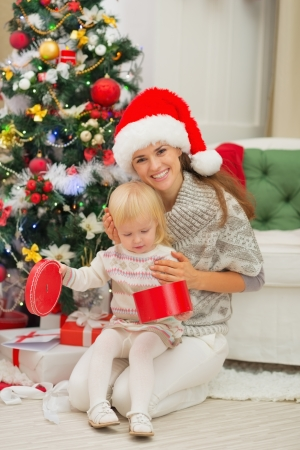 Smiling mother holding baby opening Christmas present box Stock Photo - 16577972