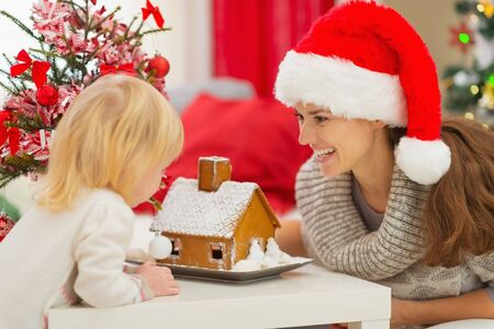 Happy mother and baby looking on Christmas Gingerbread House Stock Photo - 16577987