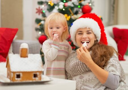 Happy mother and baby eating Christmas cookies Stock Photo - 16578008
