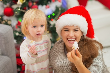 Smiling mother and baby eating Christmas cookies Stock Photo - 16578014