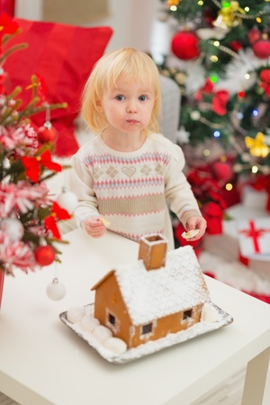 Portrait of baby eating cookies near Christmas Gingerbread house Stock Photo - 16577962
