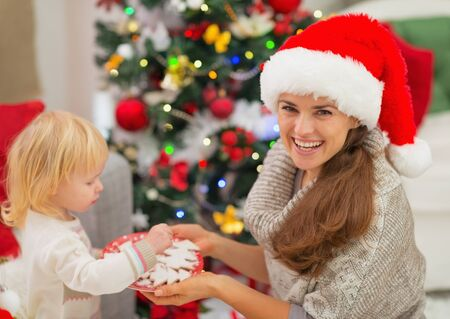 Happy mother giving baby Christmas cookies Stock Photo - 16578009