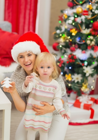 Portrait of smiling mother and baby with Christmas tree cookies Stock Photo - 16577966