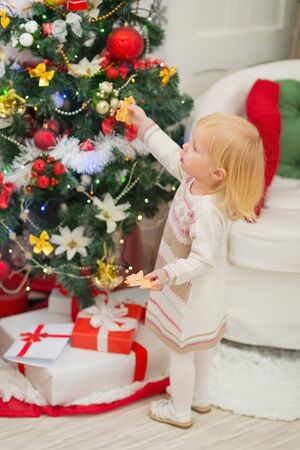eat smeared baby: Eat smeared baby eating Christmas cookies near Christmas tree Stock Photo