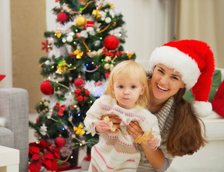 baby near christmas tree: Portrait of mother and eat smeared baby near Christmas tree Stock Photo