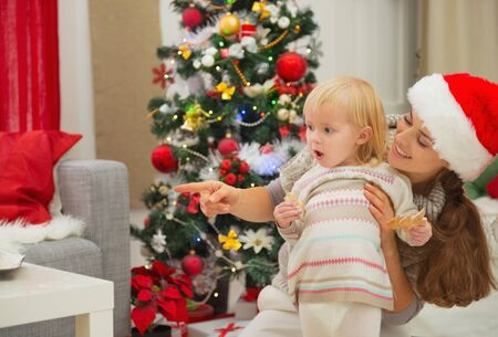 smeared baby: Eat smeared baby and mother near Christmas tree looking on copy space