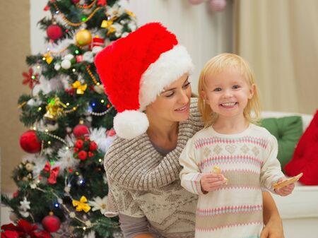 smeared baby: Retrato de la madre y el beb� feliz comer untado cerca del �rbol de Navidad