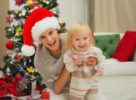 smeared baby: Retrato de la madre riendo y comer untado beb� cerca del �rbol de Navidad