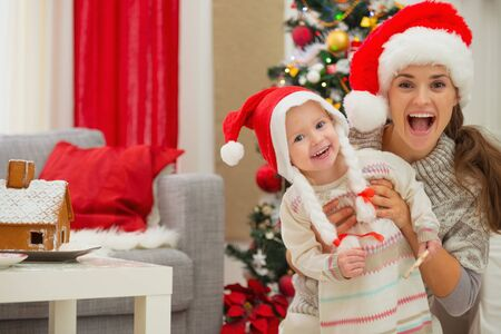 eat smeared baby: Portrait of mother and eat smeared baby in Christmas hats near Christmas tree Stock Photo