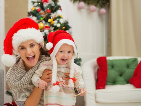 Portrait of mom and eat smeared baby girl in Christmas hats near Christmas tree photo