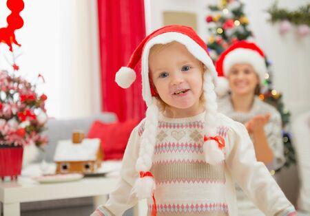 smeared baby: Retrato de ni�a comer untado en sombreros de la Navidad bailando Foto de archivo