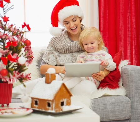 Mother showing baby something in tablet PC near Christmas tree photo