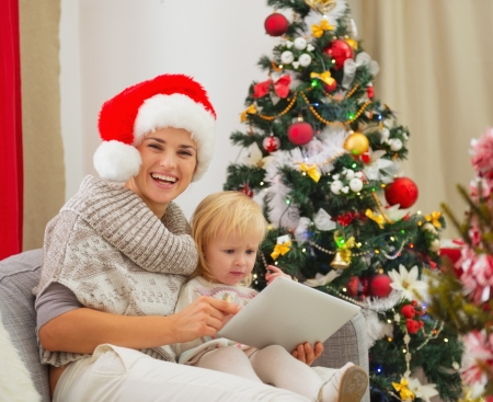 baby near christmas tree: Happy mother and baby using tablet PC near Christmas tree