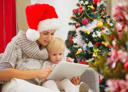 Mother and baby girl using tablet PC near Christmas tree photo