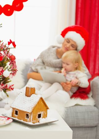 Closeup on Christmas Gingerbread house and mother and baby girl using tablet PC in background Stock Photo - 16577948