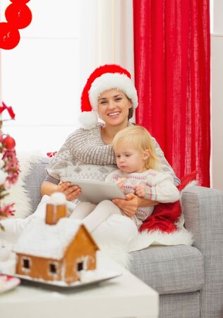 Happy mother and baby using tablet PC near Christmas tree photo