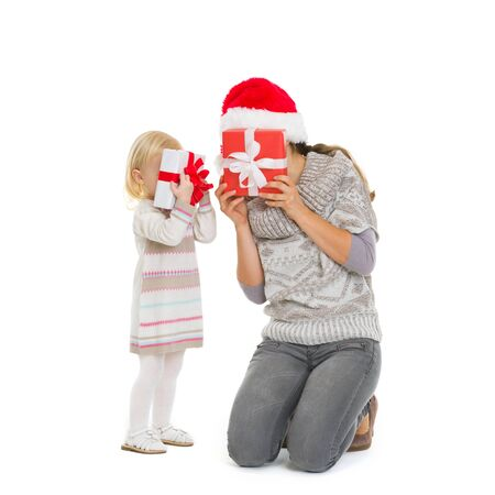 Mother and baby hiding behind Christmas gift boxes Stock Photo - 16577939