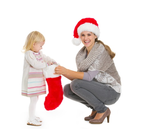Happy mother holding Christmas sock while baby girl taking out present Stock Photo - 16577945