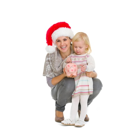 Happy mother in Christmas hat and baby girl putting coin into piggy bank Stock Photo - 16577934