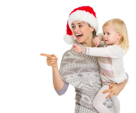 Smiling mother in Christmas hat and baby girl pointing on copy space Stock Photo - 16577952