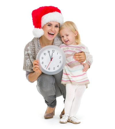 Happy mother in Christmas hat and baby girl holding clock Stock Photo - 16577949