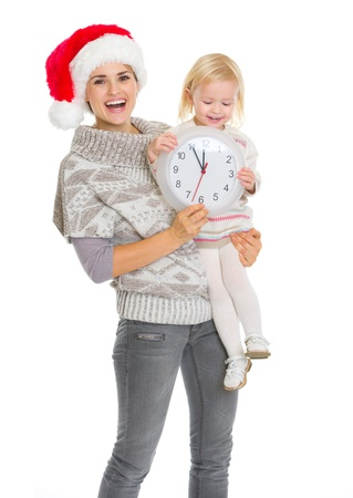 Happy mother in Christmas hat and baby girl holding clock photo