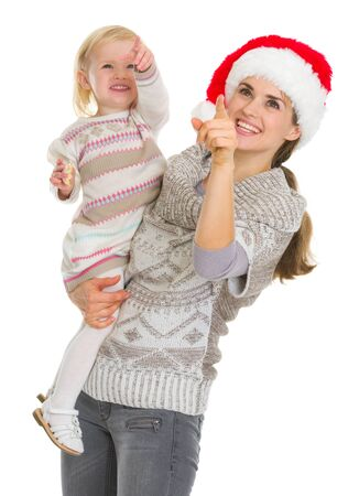 Smiling mother in Christmas hat and baby girl pointing up on copy space Stock Photo - 16577982