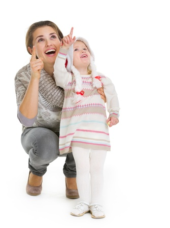 Christmas portrait of happy mother and baby girl pointing up on copy space Stock Photo - 16577967