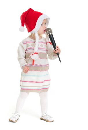 Baby girl in Christmas hat singing into microphone Stock Photo - 16577938