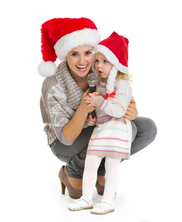 christmas baby: Christmas portrait of happy mother and baby girl singing into microphone Stock Photo