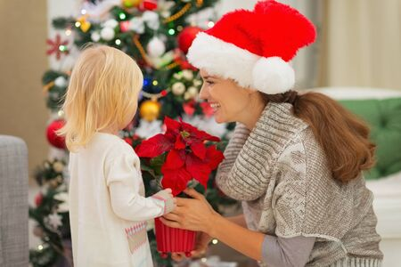 Mother and baby girl with Christmas rose near Christmas tree Stock Photo - 16577975
