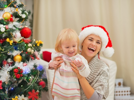 baby near christmas tree: Portrait of happy mother and baby near Christmas tree Stock Photo