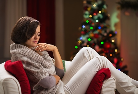Calm young woman relaxing on chair in front of Christmas tree Stock Photo - 16710957