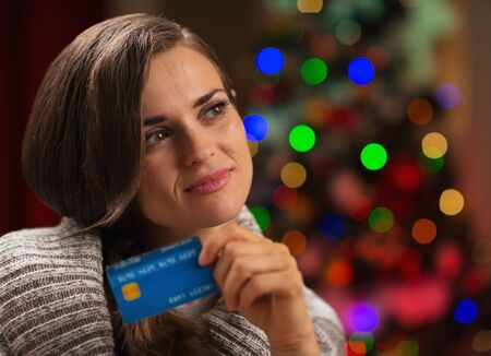 Portrait of thoughtful woman with credit card in front of Christmas lights Stock Photo - 16710954