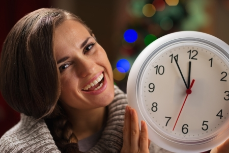 show time: Portrait of smiling young woman showing clock in front of Christmas lights Stock Photo