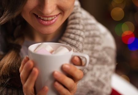 Closeup on hot chocolate with marshmallows in hand of happy girl Stock Photo - 16711014