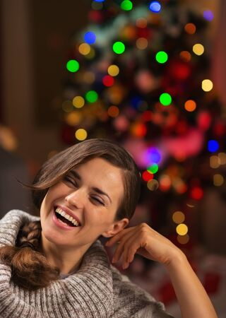 Portrait of smiling young woman in front of Christmas lights Stock Photo - 16710963