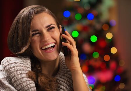 Smiling young woman speaking mobile phone in front of Christmas lights photo