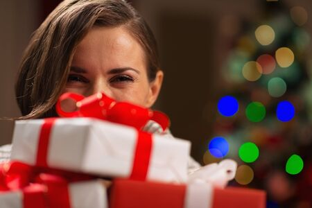Girl hiding behind Christmas present boxes Stock Photo - 16710997