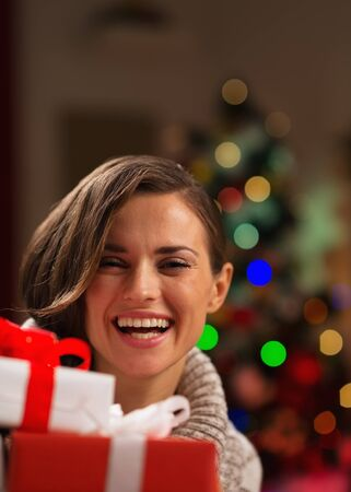 Happy young woman looking out from Christmas gift boxes photo