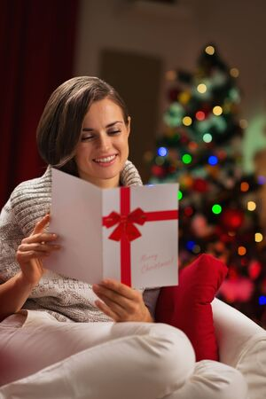 Happy young woman reading Christmas postcard Stock Photo - 16710955