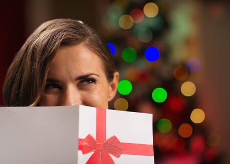 Girl hiding behind Christmas postcard Stock Photo - 16711005